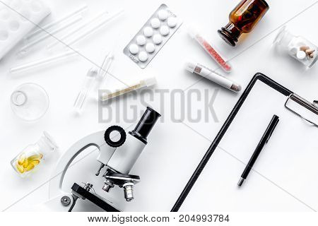 Laboratory test. Microscope, pills, test tube on white background top view.