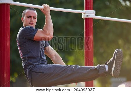 Serious athletic man hanging on hands on crossbars on a blurred park background. Exercising young man in action.