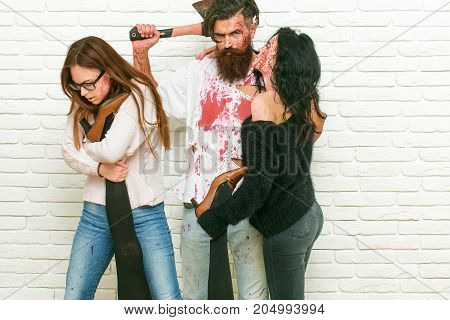 Halloween zombie people of bearded man long beard brutal caucasian hipster with moustache hold axe and bloody women with wounds and red blood female legs on white brick wall background