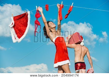 New year guy with muscular body on blue sky. Christmas man and woman family. Couple in love of man and girl hanging clothes for drying. Laundry and dry cleaning. Xmas red costume on rope with pin.