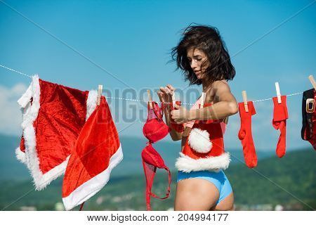 New year girl on sunny blue sky. Christmas woman with buttocks outdoor. Laundry and dry cleaning. Santa claus girl hanging clothes for drying. Xmas red costume on rope with pin.