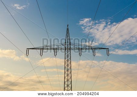 Silhouette of a high voltage tower at cloudy sky at sunset