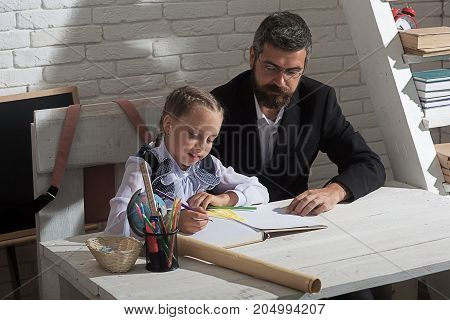 Classroom and home education concept. Schoolgirl and tutor with smiling faces learn to write. Man and kid work at desk with school supplies. Girl and teacher in study room on white brick background