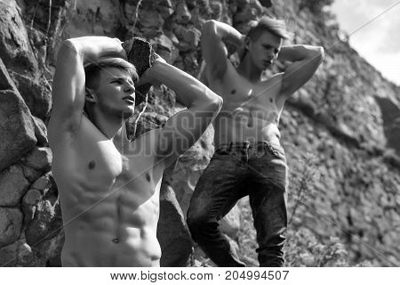 Muscular Twins On Mountain Rocks