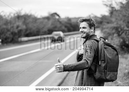 Young guy with beard on sexy smiling handsome face in casual clothes black backpack standing near road way hitchhiking autostop with hand outdoor