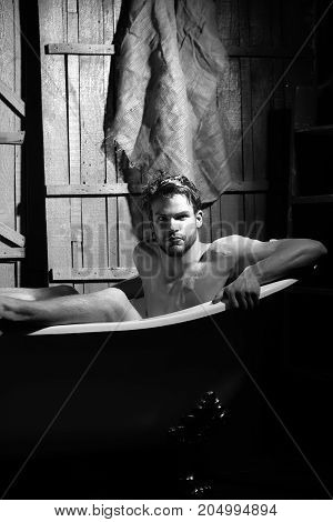 One handsome serious sensual sexy muscular young man with beautiful bare body sitting in white bath tub with foam taking shower looking forward indoor on wooden wall backdrop vertical picture