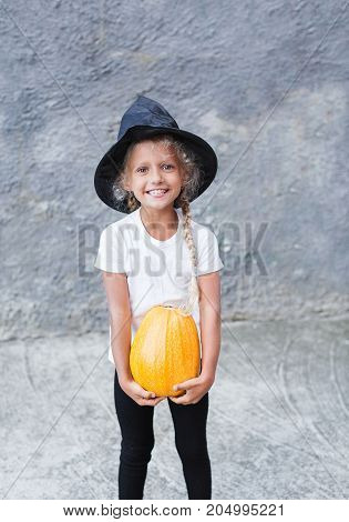 Girl in Halloween costume having fun. A little girl in a witch costume is playing with a pumpkin. Little girl in witch costume playing outdoor.