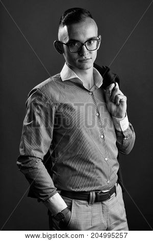 young fashion businessman with nerd glasses and stylish hairdo in pink shirt holding jacket posing on grey background
