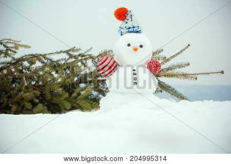 Christmas Tree And Snowman On White Sky On Snowy Background