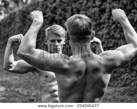 Muscular young twins bodybuilders with beautiful sexy body and bare torso posing outdoor sunny day on natural background