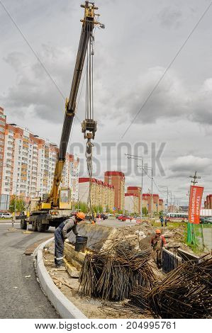 Tyumen, Russia - June 1, 2017: JSC Mostostroy-11. Construction of two-level outcome on bypass road on Fedyuninskogo and Permyakova streets intersection. Construction worker and crane at building site