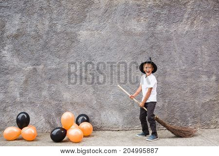 Boy in Halloween costume having fun. A little boy in a witch costume is playing. Boy witch with a broom on halloween