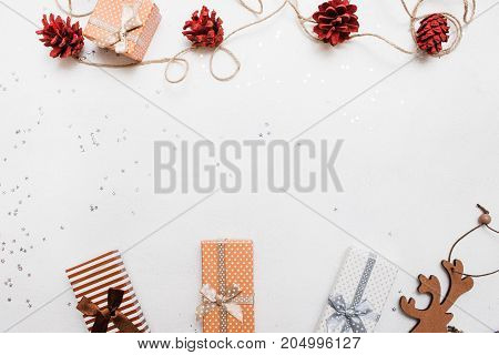 Festive background of Christmas holiday. Gift boxes on white background with silver star tinsels and strobila decoration above, top view with copy space. Celebrations, New Year, festival concept
