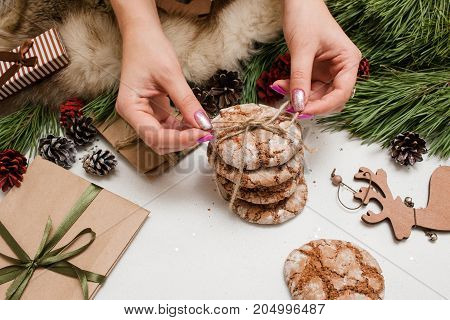 Preparing festive presents for Christmas and New Year. Sweet cakes binding by unrecognizable woman near decoration from pine and wrapped gifts, close up. Congratulation and homemade decor concept