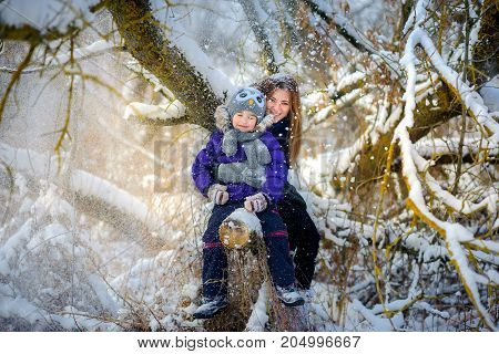 mother together with the daughter poses under a tree in the mnezhny wood beautiful snow falls