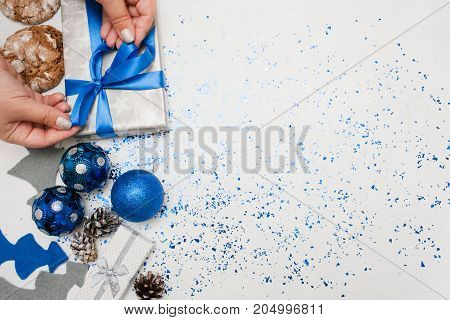 Preparing Christmas decor and gifts top view. Woman binding present by festive tape, ornament blue balls, felt fir tree, cakes and tinsel spread around with copy space. Handmade decoration concept