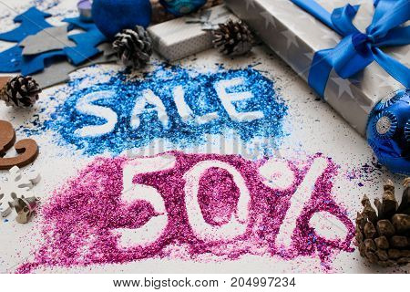 Sales on Christmas and New Year holidays, close up. Colorful festive decoration with informative inscription of 50 pct discount for shop-windows, shopping malls and advertizing background concept