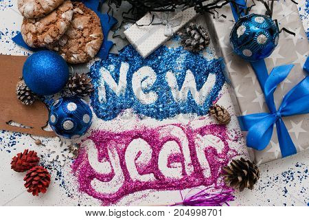 New Year inscription. Decor and gifts backdrop. Top view wrapped presents and different handmade ornaments, bright spangles spread around. Festive background of holiday decoration concept