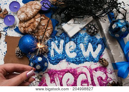 Firework sparkler holding in hand on festive backdrop top view. Wrapped presents and different handmade decoration with bright New Year inscription. Holiday decor and celebration concept