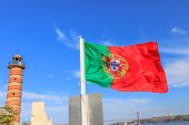 Symbols and icons in Lisbon city: Belem Lighthouse, flag of Portugal waving, Discoveries Monument, Bridge of 25 April and Tagus river. Belem District, Lisbon, Portugal, Europe. poster