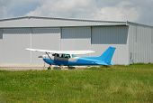 Light Cessna propeller driven airplane parked at warehouse poster