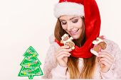 Woman wearing red xmas hat playing with gingerbread cookies little snowman and claus. Happy girl awaiting christmas holidays poster