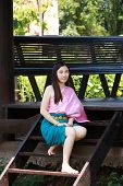 Thai Asian polite woman with smile face in traditional costume of Thailand at waterfront pavilion front of riverside ancient house near the river. Beautiful Asia female model in her 20s. poster