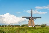 Eight-sided thatched historic windmill De Oude Doorn near the Dutch village of Almkerk was built around 1700 and restored in 2012. The wooden mill on a high brick base now has no role in the drainage of the polder Den Doorn. poster