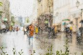 Rainy day in city. People seen through raindrops on glass. Selective focus on the raindrops. Silhouette of girl in bright beautiful coat poster