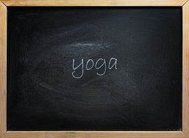 Yoga text written on black school board with wooden frame.