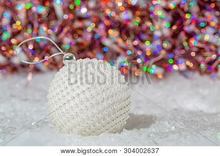 Christmas Decoration.white Ball With Nacre Pearls On A Snow And Beautiful Blurred Colorful Backgroun