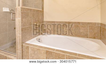 Panorama Frame Interior Of A Warm Toned Bathroom With Built In Gleaming White Bathtub
