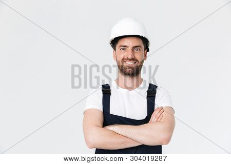 Confident bearded builder man wearing overalls and hardhat standing isolated over white background, arms folded