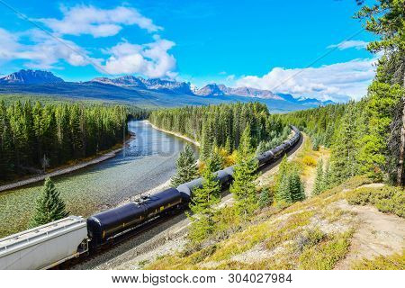 Long Freight Train Moving Along Bow River In Canadian Rockies ,banff National Park, Canadian Rockies