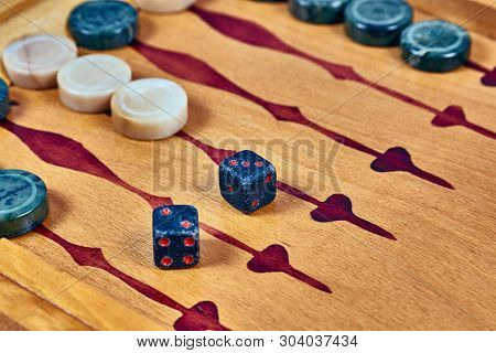 Backgammon Game. Game Dice Made Of Stone Lie On The Backgammon Board Against The Background Of Check