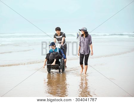 Older Brother And Sister Walking Younger Disabled Brotherin Wheelchair In The Water Along The Beach