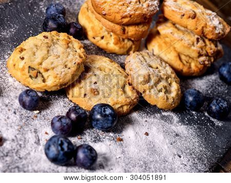Serving food on slate onto wooden table. Oatmeal cookies biscuit with blueberry on picnic dark tiles countrylike. Chocolate Xmas holiday chip cookies. Perfect product. Confectionery production.
