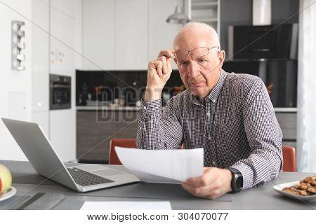 Senior Man Worried About Bills And Savings. Finances, Savings, Insurance Concept
