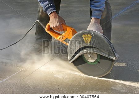 Man cutting control groove in concrete slab