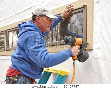 Carpenter using nail gun to install trim around windows