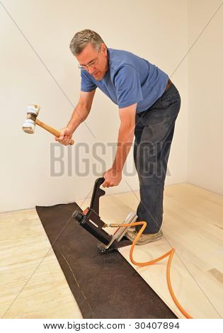 Man installing hardwood floor using pneumatic power nailer