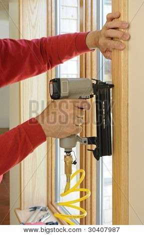 Nail gun being used to install wood trim around windows with finishing nails