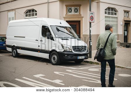 Strasbourg, France - Apr 5, 2017: Adult Man Crossing Street In Front Of White Mercedes-benz Sprinter
