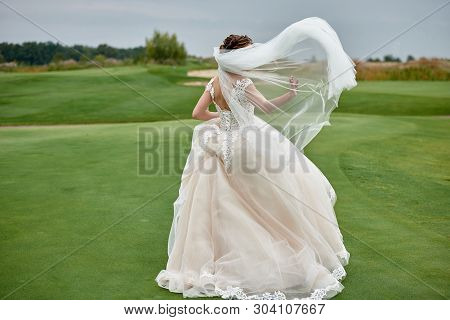 Full Length Body Portrait Of Beautiful Bride In White Wedding Dress With Long Veil Running On Green