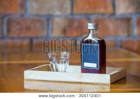 A Glass And Coffee In A Bottle Ready For Serve To Customer,brick Wall Background.