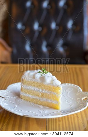 Coconut Cake On White Plate And Wooden Table