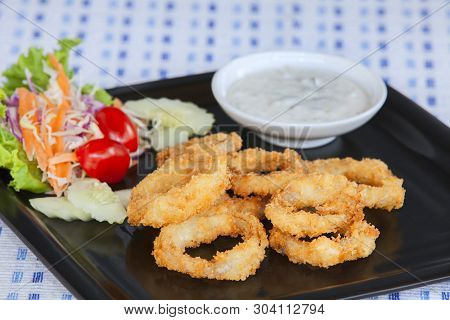 Fried With Onion Sauce Place On A Plate Decorated With Vegetables And Dressing.