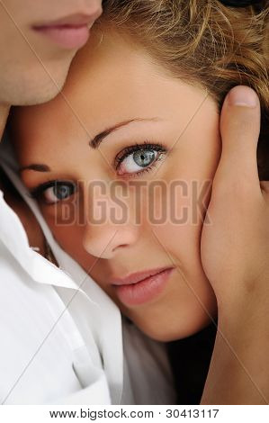 Closeup image of a teenage girl and boy holding her head