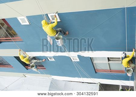 Painters Hanging On Roll, Painting Color On Wall. Facade Builder With Roller Brush, Working On High