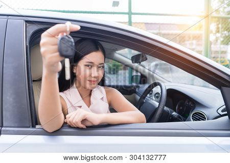 Happy Woman Driving Car Hand Holding Key Looking At Camera Focus On Face. Young Asian Woman Showing